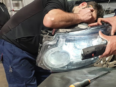 Mechanic inspecting headlight unit from Landrover